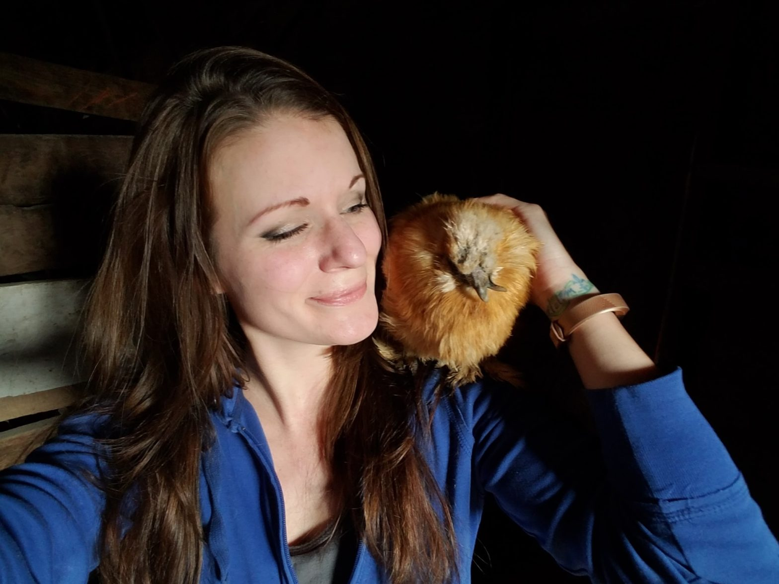 Jessica Hawkes cuddles with a chicken on her shoulder at her Animal Sanctuary in New Rockford, ND.