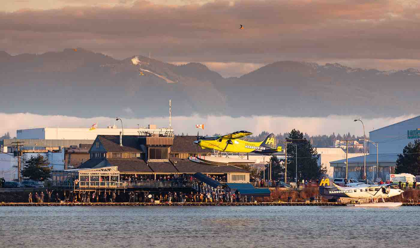 A yellow Harbour Air seaplane glides just above the water of the Fraser River in Vancouver, Canada, mist an mountains in the distance, and a crowd of people on bleachers in front of buildings line the riverbank. The image captured and provided by Harbour Air depicts the first flight by an all-electric commercial aircraft.