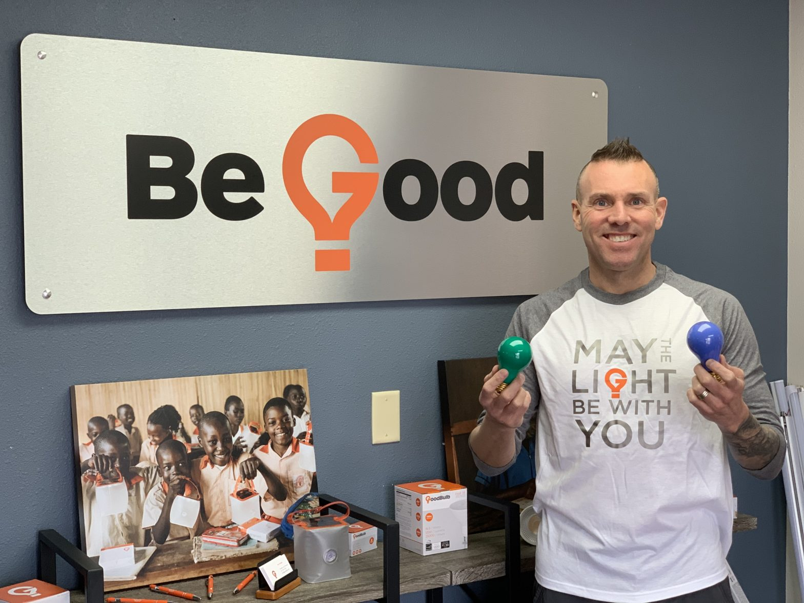 "Tom Enright poses with a blue and green lightbulb, with a sign reading ""Be Good"" behind him."