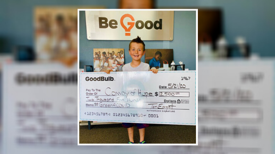 "GoodBulb founder Tom Enright's son Chase holds up a large check reading $2,500 for Convoy of Hope. A sign in the background reads ""Be Good."""