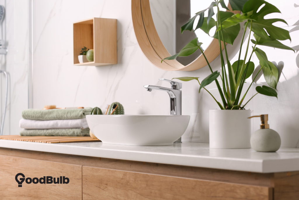 A bathroom vanity with a green plant next to the sink, and a dark gray GoodBulb logo in the left hand corner.