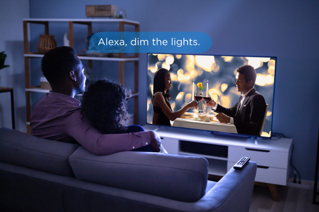 A couple watches a movie, with a voice bubble that says 'Alexa, dim the lights.'